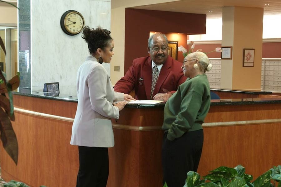 A woman and man talking to a resident in the lobby at York House